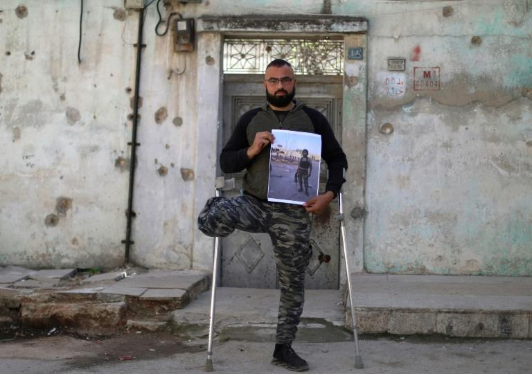 In Idlib city, former rebel fighter Mohammed al-Hamid holds a picture showing him before the war in a military uniform and holding a weapon