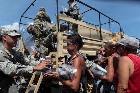 Soldiers of Puerto Rico's national guard distribute relief items to people, after the area was hit by Hurricane Maria in San Juan, Puerto Rico