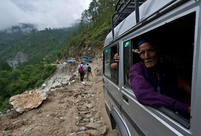 An elderly Indian man looks out as he drives past a damaged section of road between Rudraprayag and Gauchar, at Gauchar on June 25, 2013, after flash flooding hit the northern Indian state of Uttarakhand. Some 1000 people have been killed in flash floods and landslides in northern India, as a top official warned that rebuilding of the devastated Himalayan region would take years. TOPSHOTS AFP PHOTO/MANAN VATSYAYANA