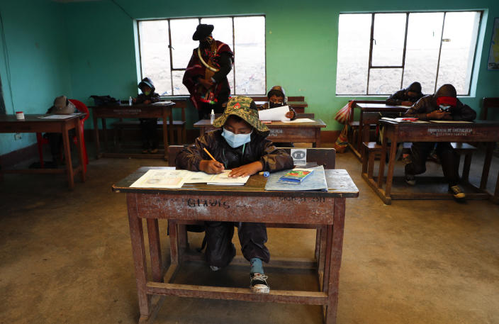 An Aymara Indigenous parent watches over students during the first week back to in-person classes with pupils wearing new protective uniforms amid the COVID-19 pandemic near Jesus de Machaca, Bolivia, Thursday, Feb. 4, 2021. (AP Photo/Juan Karita)
