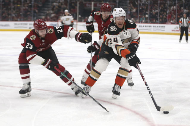 Anaheim Ducks' Carter Rowney (24) beats the Arizona Coyotes' Oliver Ekman-Larsson (23) and Clayton Keller (9) to the puck during the first period of an NHL hockey game Wednesday, Nov. 27, 2019, in Glendale, Ariz. (AP Photo/Darryl Webb)