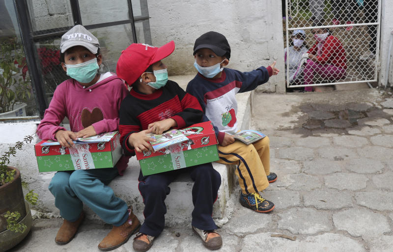 Children, wearing protective face masks as a precaution against the spread of the new coronavirus, sit holding boxes filled with toys and books donated by private organizations, as they wait for their parents in Quito, Ecuador, Thursday, April 23, 2020. (AP Photo/Dolores Ochoa)