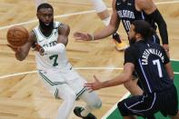 Boston Celtics' Jaylen Brown, left, passes off against Orlando Magic's Michael Carter-Williams during the first half on an NBA basketball game, Sunday, March 21, 2021, in Boston. (AP Photo/Michael Dwyer)