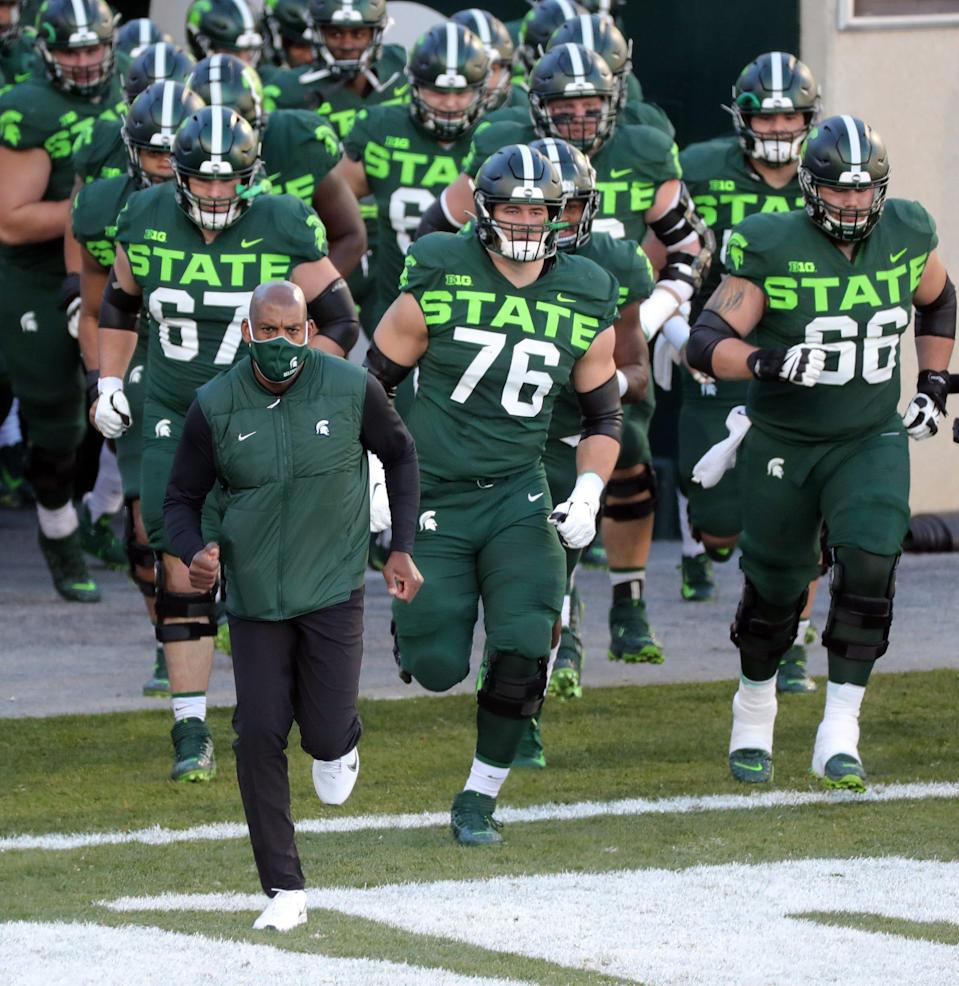 Michigan State coach Mel Tucker leads his team onto the field before MSU's 29-20 win over Northwestern at Spartan Stadium on Saturday, Nov. 28, 2020.