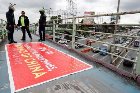 "Traffic enforcers stand next to a banner reading ""Welcome to the Philippines, Province of China"" after removing it from an overpass along the C5 road intersection in Taguig, Metro Manila, Philippines July 12, 2018. REUTERS/Erik De Castro"