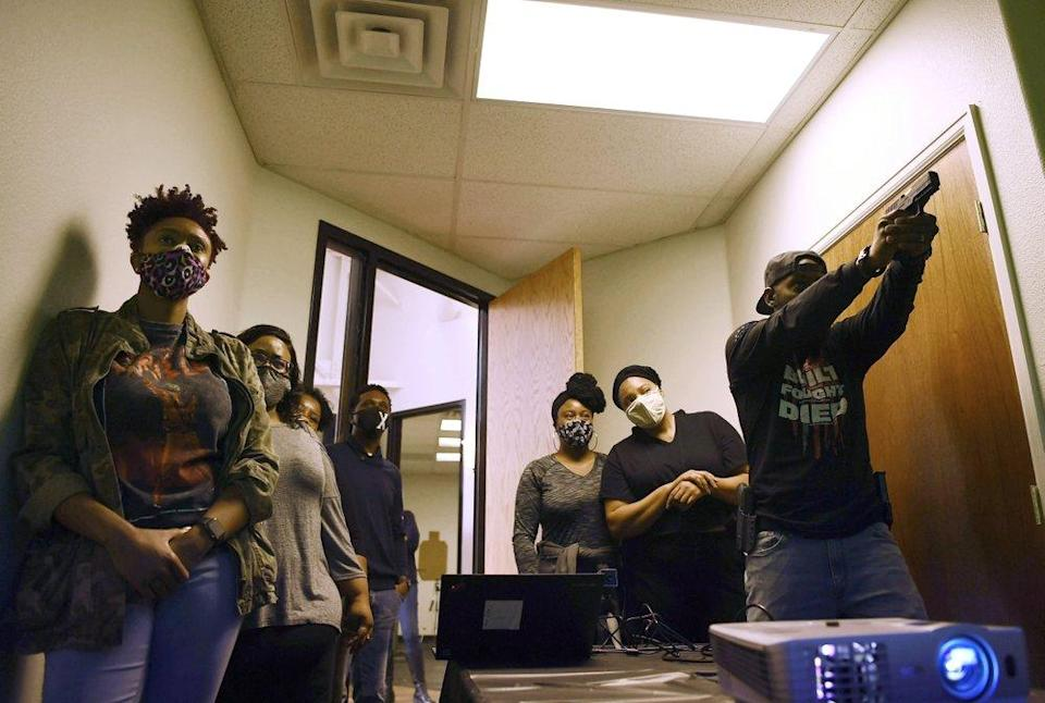 Anubis Heru, right, lead trainer, runs a pistol and safety class at 1770 Armory and Gun Club, Colorado's first Black-owned shooting range, Saturday, Oct. 24, 2020 in Denver. (Rachel Ellis/The Denver Post via AP)