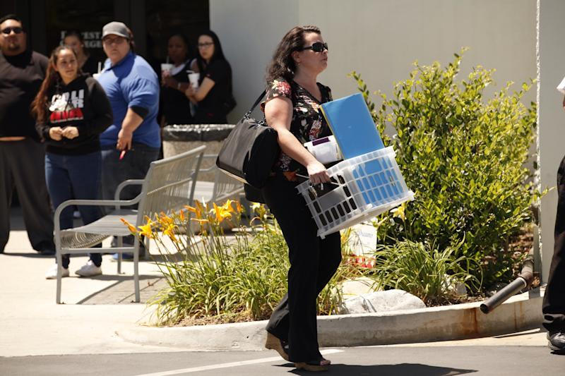 CITY OF INDUSTRY, CA APRIL 27, 2015 -- Teacher Christina Ledoux carries her belongings as Students gathered with teachers that came to collect their personal items at Everest College in City of Industry, one of the Corinthian Colleges that closed on Monday. April 27, 2015. (Al Seib / Los Angeles Times via Getty Images)