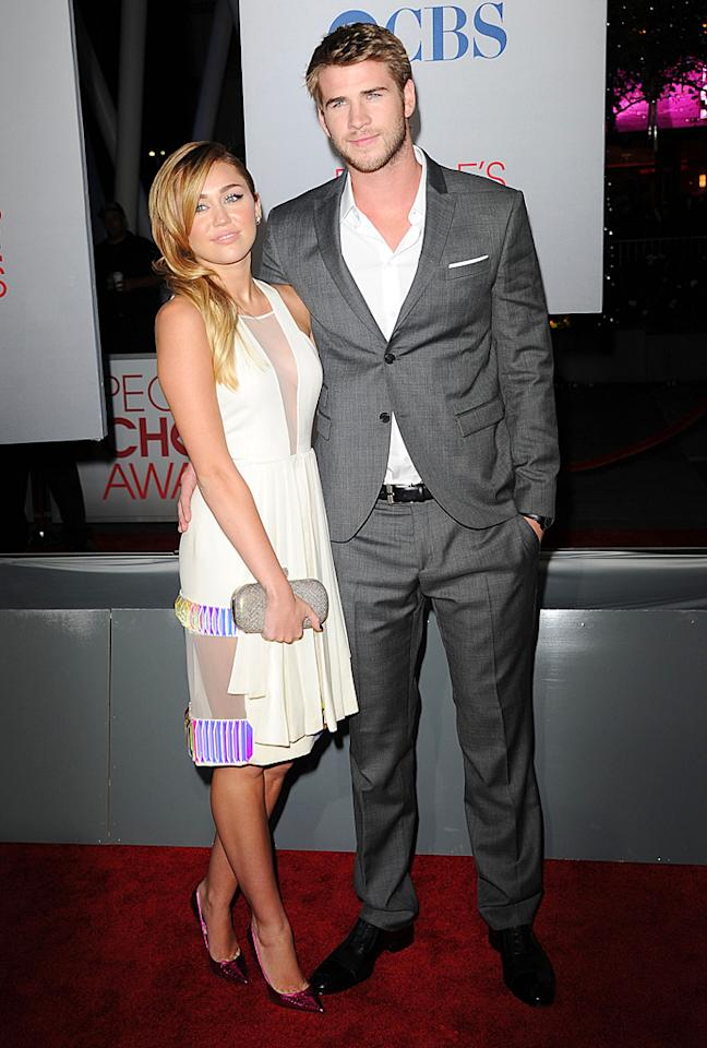 All eyes were on Miley Cyrus as she arrived at the 2012 People's Choice Awards wearing a cream halter dress by David Koma, which <span></span>featured a plunging neckline and a multi-colored mesh panel in the back. The teen queen accessorized with metallic Jimmy Choo heels and her gorgeous main squeeze, Liam Hemsworth. (01/11/2012)