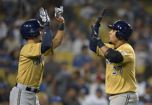 Milwaukee Brewers' Carlos Gomez, right, is congratulated by teammate Norichika Aoki, of Japan, after hitting a two-run home run during the seventh inning of their baseball game against the Los Angeles Dodgers, Saturday, April 27, 2013, in Los Angeles. (AP Photo/Mark J. Terrill)
