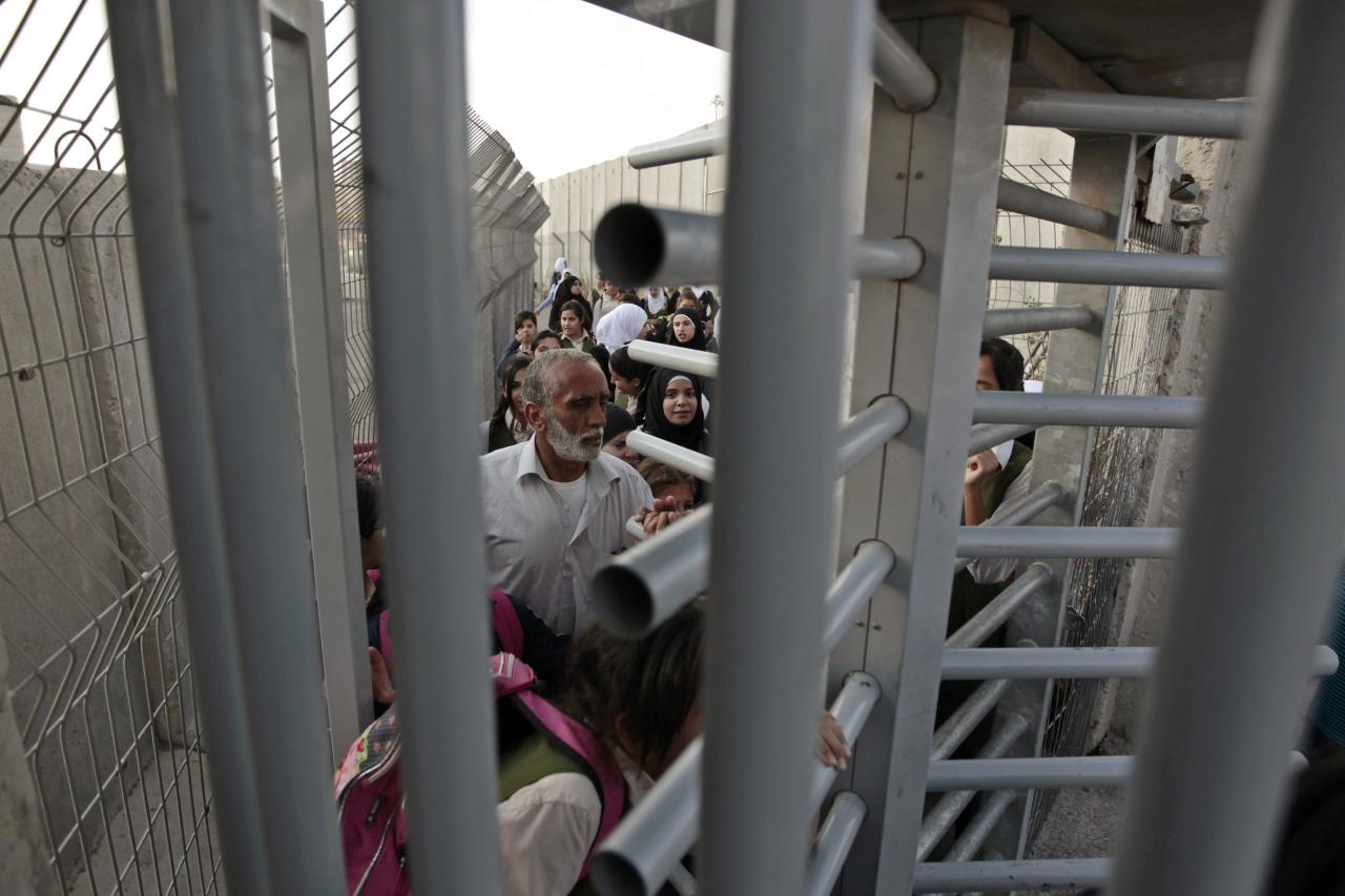 Palestinians wait to cross through an Israeli checkpoint as they enter Shuafat refugee camp in the West Bank near Jerusalem November 21, 2013. Marooned behind the wall, Israel's controversial barrier, the Shuafat refugee camp reveals the state's uneven treatment of Arab and Jewish neighbourhoods, creating a de facto partition of Jerusalem, which is the epicentre of the Middle East conflict. Picture taken November 21, 2013. REUTERS/Ammar Awad (WEST BANK - Tags: POLITICS SOCIETY)