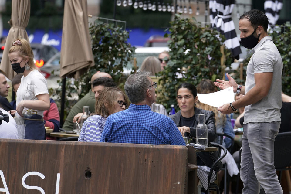 FILE - In this May 2, 2021, patrons at a sidewalk cafe are seated without masks in Boston. COVID-19 deaths in the U.S. have tumbled to an average of just over 600 per day — the lowest level in 10 months — with the number of lives lost dropping to single digits in well over half the states and hitting zero on some days. (AP Photo/Steven Senne, File)