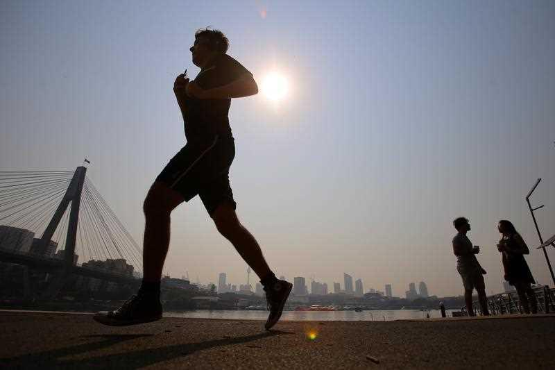 Joggers in Blackwattle Bay as smoke haze from bushfires hangs over the CBD during hot weather in Sydney.