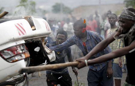 Protesters destroy a car belonging to a policeman after they intercepted him at a barricade during demonstrations against the ruling CNDD-FDD party's decision to allow President Pierre Nkurunziza to run for a third five-year term in office, in Bujumbura, Burundi April 30, 2015. REUTERS/Thomas Mukoya
