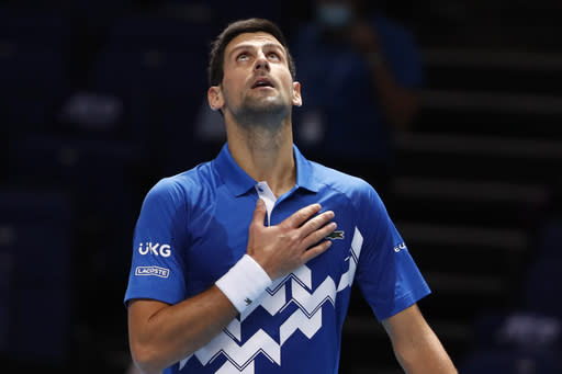 Novak Djokovic of Serbia celebrates winning match point against Alexander Zverev of Germany during their singles tennis match at the ATP World Finals tennis tournament at the O2 arena in London, Friday, Nov. 20, 2020. (AP Photo/Frank Augstein)