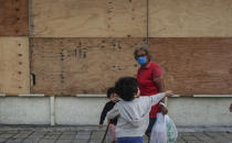 A family walks in front of a supermarket with its windows covered with plywood as Tropical Storm Zeta approaches Cancun, Mexico, Monday, Oct. 26, 2020. A strengthening Tropical Storm Zeta is expected to become a hurricane Monday as it heads toward the eastern end of Mexico's resort-dotted Yucatan Peninsula and then likely move on for a possible landfall on the central U.S. Gulf Coast at midweek. (AP Photo/Victor Ruiz Garcia)