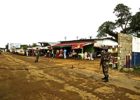 Soldiers from the Liberian army monitor a border checkpoint as part of Operation White Shield to control the Ebola outbreak, at an entrance to Bomi County in northwestern Liberia