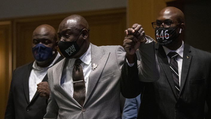 Attorney Ben Crump (C) holds up the hand of Philonise Floyd (R), and is joined by Rodney Floyd (L) as they enter a press conference at the Minneapolis Convention Center on March 12, 2021 in Minneapolis, Minnesota. (Stephen Maturen/Getty Images)