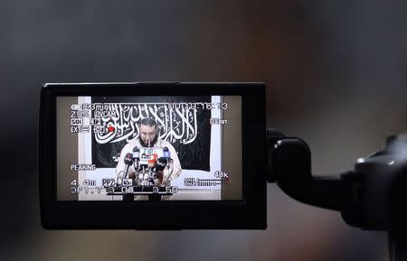 Mohamed Zahawi, head of the Benghazi brigade of Ansar al-Sharia, is seen on the screen of a camera as he delivers a statement in Benghazi
