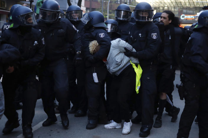Police officers detain a demonstrator during a May Day rally in Berlin, Germany, Saturday, May 1, 2021. (AP Photo/Markus Schreiber)