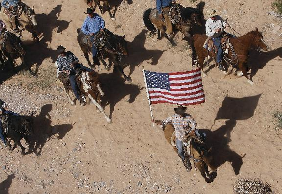 FILE - In this April 12, 2014, file photo, the Bundy family and their supporters fly the American flag as their cattle is released by the Bureau of Land Management back onto public land outside of Bunkerville, Nev. A federal judge in Nevada is considering crucial rulings about what jurors will hear in the trial of six defendants accused of stopping U.S. agents at gunpoint from rounding up cattle near Cliven Bundy's ranch in April 2014. (Jason Bean/Las Vegas Review-Journal, via AP, File)