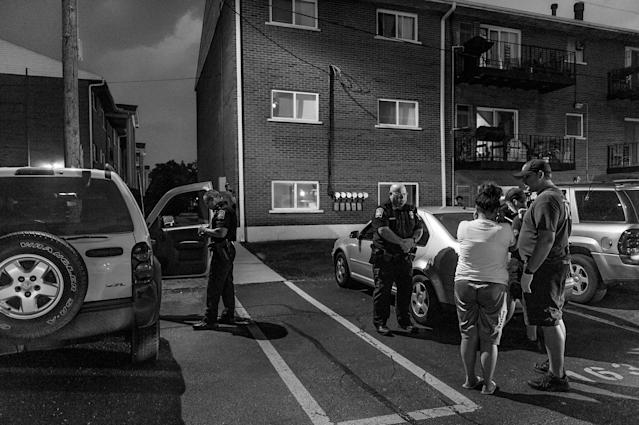 <p>In the parking lot outside Old Crow Bar, the Middletown Fire Department responds to a call about a possible heroin overdose. The woman insists that she's fine — she doesn't want to go to the hospital. (Photograph by Mary F. Calvert for Yahoo News) </p>