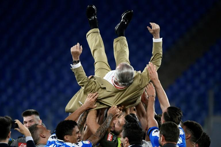 Napoli's players throw club President Aurelio De Laurentiis in the air as they celebrate after the Italian Cup trophy