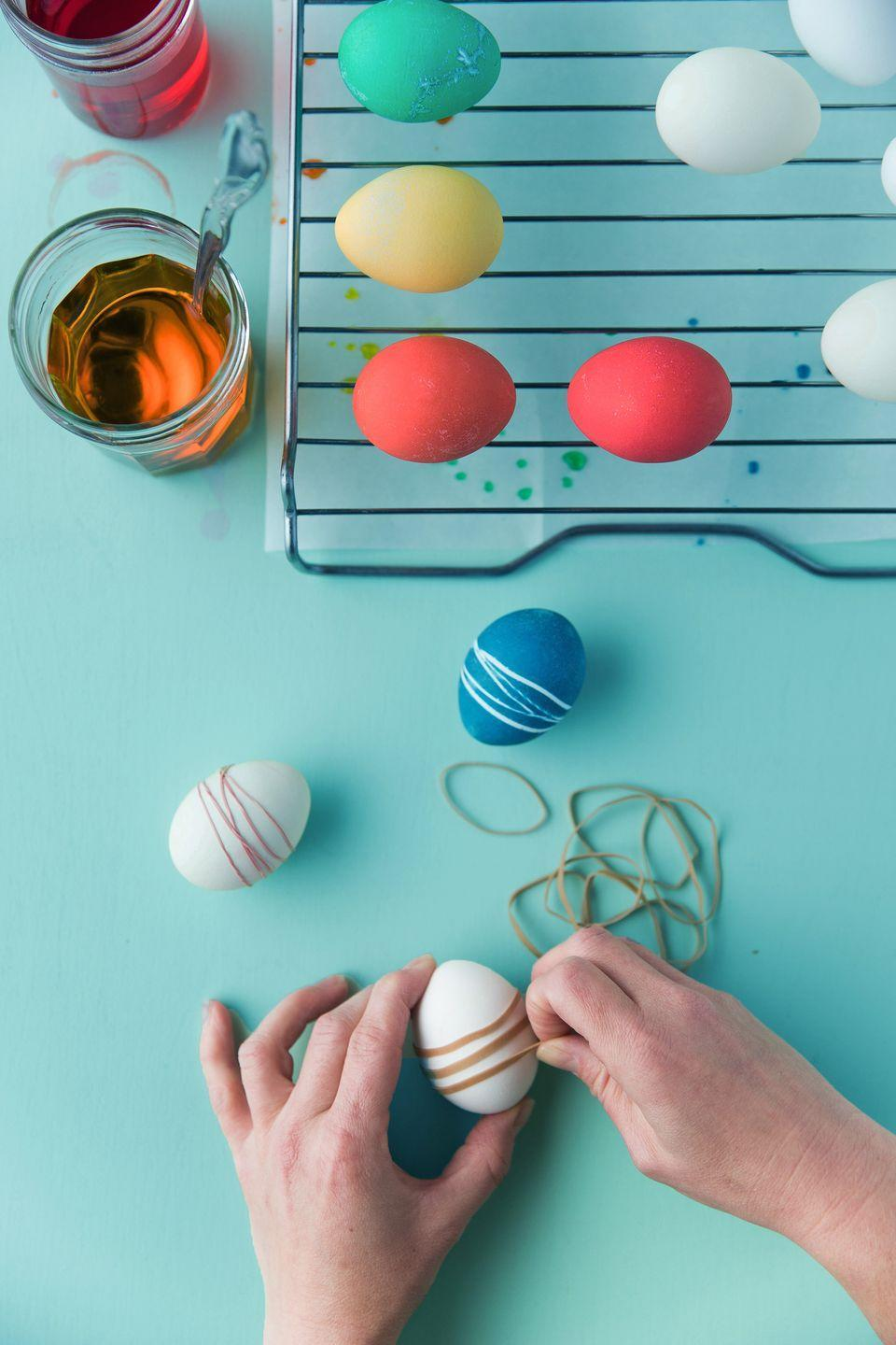 "<p>Wrap rubber bands tightly around the eggs before dyeing, or between coats of dye. To ensure a good seal, make sure they're snug—the tighter, the better. Wide, flat rubber bands will help you keep the rubber band from twisting too much.</p><p><a class=""link rapid-noclick-resp"" href=""https://www.amazon.com/AmazonBasics-Assorted-Color-Rubber-Bands/dp/B074B1KCXD/?tag=syn-yahoo-20&ascsubtag=%5Bartid%7C10050.g.26810304%5Bsrc%7Cyahoo-us"" rel=""nofollow noopener"" target=""_blank"" data-ylk=""slk:SHOP RUBBER BANDS"">SHOP RUBBER BANDS</a></p>"
