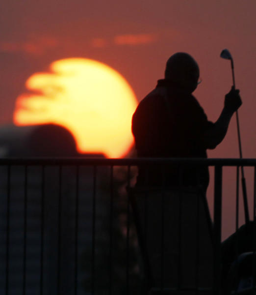 A lone golfer puts away his iron as the sun sets over a driving range on Thursday, Aug. 16, 2012, in the southeast Denver suburb of Englewood, Colo. Wildfires across the intermountain West have made for colorful sunsets over the past few days. (AP Photo/David Zalubowski)