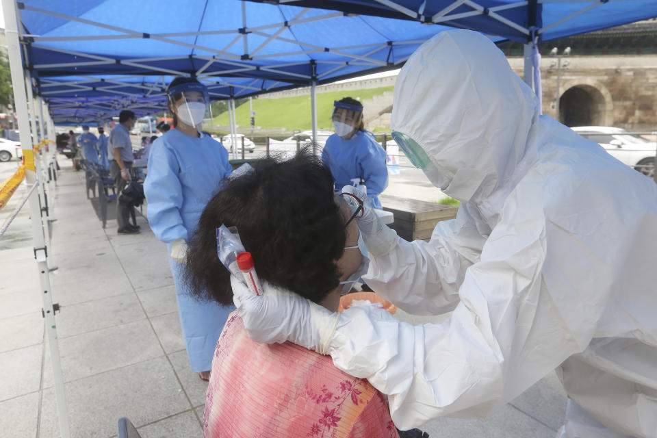 A health official wearing protective gear takes samples from a woman during the COVID-19 testing at a makeshift clinic in Seoul, South Korea, Monday, Aug. 10, 2020. (AP Photo/Ahn Young-joon)