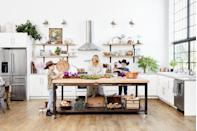 <p>In addition to a wall of steel-framed windows, these homeowners outfitted this white kitchen with handmade shelves, cabinet doors, hardware, and a massive island that can be wheeled away when prep is over and playtime begins. </p>
