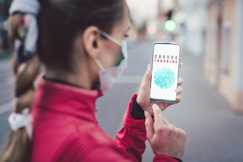 Woman using a phone with the coronavirus tracking app installed walking a city street