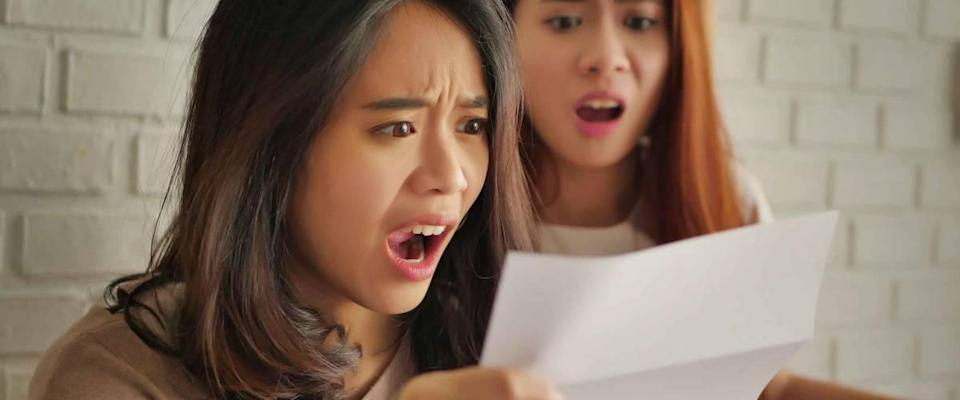 frustrated, shocked women looking at expensive bill or debt notice invoice