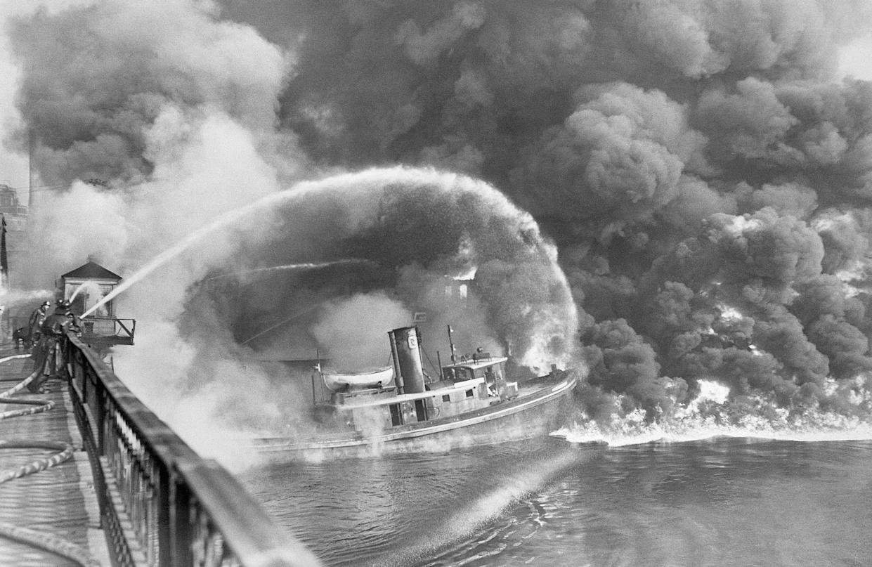 Firemen spray water on a tug boat as a fire, ignited in an oil slick on the Cuyahoga River, consumes the docks at the Great Lakes Towing Co., Cleveland, June 25, 1952. (Photo: Bettmann Archive via Getty Images)