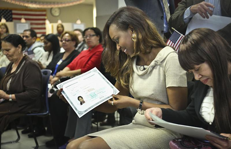 "Immaculee Ilibagiza,second from right, reacts after receiving her citizenship certificate during the U.S. Citizenship and Immigration Services naturalization ceremony on Wednesday, April 17, 2013, in New York. ""Who would know that this fantasy would finally happen,"" said Ilibagiza, author of the best seller ""Left to Tell, Discovering God Amidst the Rwandan Holocaust."" She sought asylum in the U.S. after fleeing the 1994 Rwandan genocide, which claimed more than 500,000 lives. (AP Photo/Bebeto Matthews)"