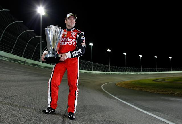HOMESTEAD, FL - NOVEMBER 21: Tony Stewart, driver of the #14 Office Depot/Mobil 1 Chevrolet, poses with the Championship trophy after winning the NASCAR Sprint Cup Series Ford 400 and the 2011 Series Championship at Homestead-Miami Speedway on November 21, 2011 in Homestead, Florida. (Photo by Chris Graythen/Getty Images)