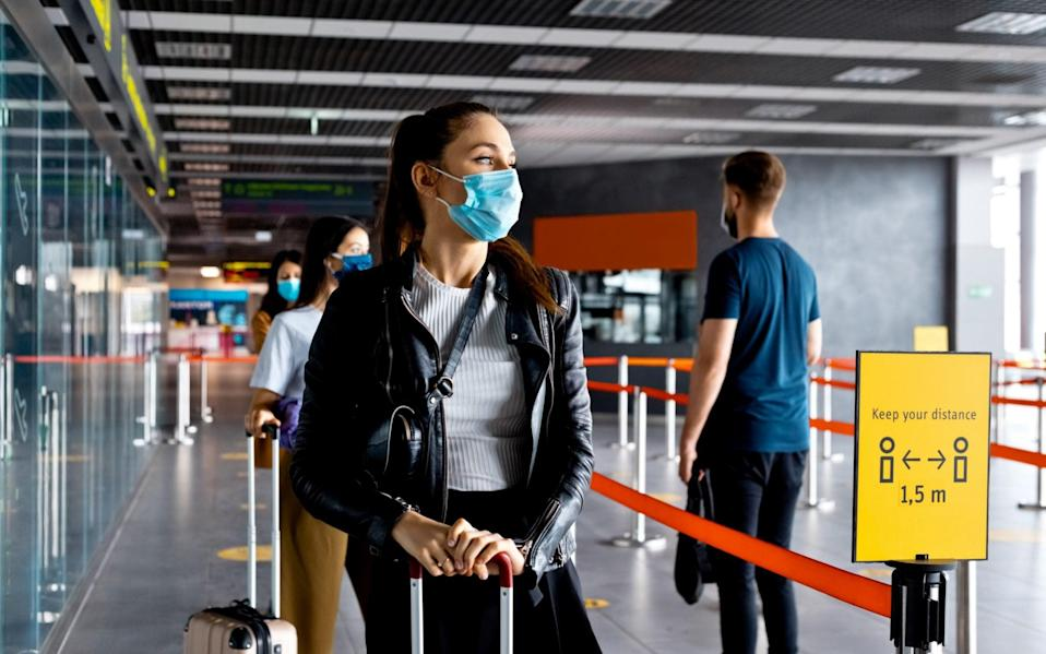 Passengers wearing masks queue in line at the airport - izusek/Getty