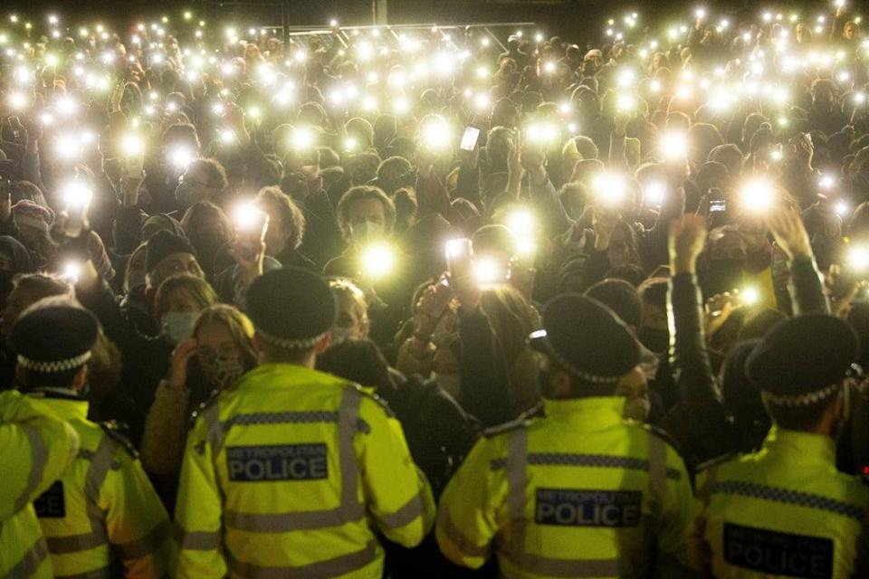 People in the crowd turn on their phone torches as they gather in Clapham Common for a vigil for Sarah Everard (PA) (PA Wire)