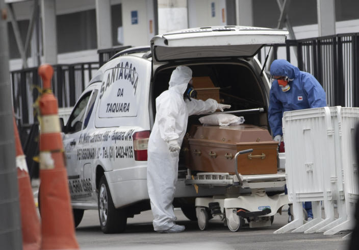Funeral workers wearing protective gear as a precaution amid the new coronavirus pandemic push the remains of a COVID-19 victim into a funeral car at a field hospital in Leblon, Rio de Janeiro, Brazil, Thursday, June 4, 2020. (AP Photo/Silvia Izquierdo)