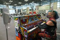Gravity, the Queen of Love and Hope performer and music artist from Brooklyn, plays a Sing For Hope piano while waiting during the observation period after getting her first dose of a COVID-19 vaccination at the Jacob K. Javits Convention Center, Thursday, March 18, 2021, in New York. Gravity said she set a goal during the pandemic of live-streaming her art at least ten minutes a day. (AP Photo/Kathy Willens)