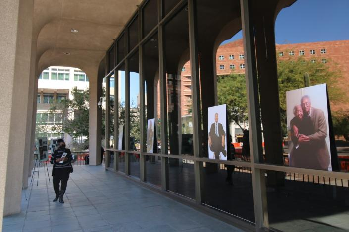 A woman walks past pictures of the late civil rights leader Calvin C. Goode, who was laid in state in front of Calvin C. Goode Municipal Building in Phoenix on Saturday, Jan. 9, 2021. Family members and members of the community attended the public, socially distanced viewing for Goode who died on Wednesday, Dec. 23, 2020. He was 93. (AP Photo/Cheyanne Mumphrey)