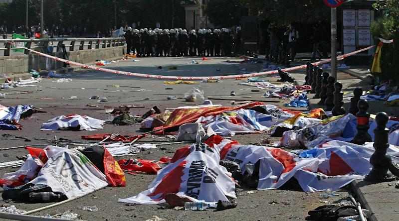 The bodies of bomb attack victims are covered with banners and flags as Turkish riot police secure the area near the main train station in Turkey's capital Ankara, on October 10, 2015 (AFP Photo/Adem Altan)