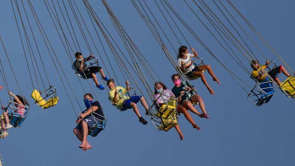 PHOTO: People wearing masks ride attractions at an amusement pier on July 3, 2020, in Wildwood, N.J. (Mark Makela/Getty Images)