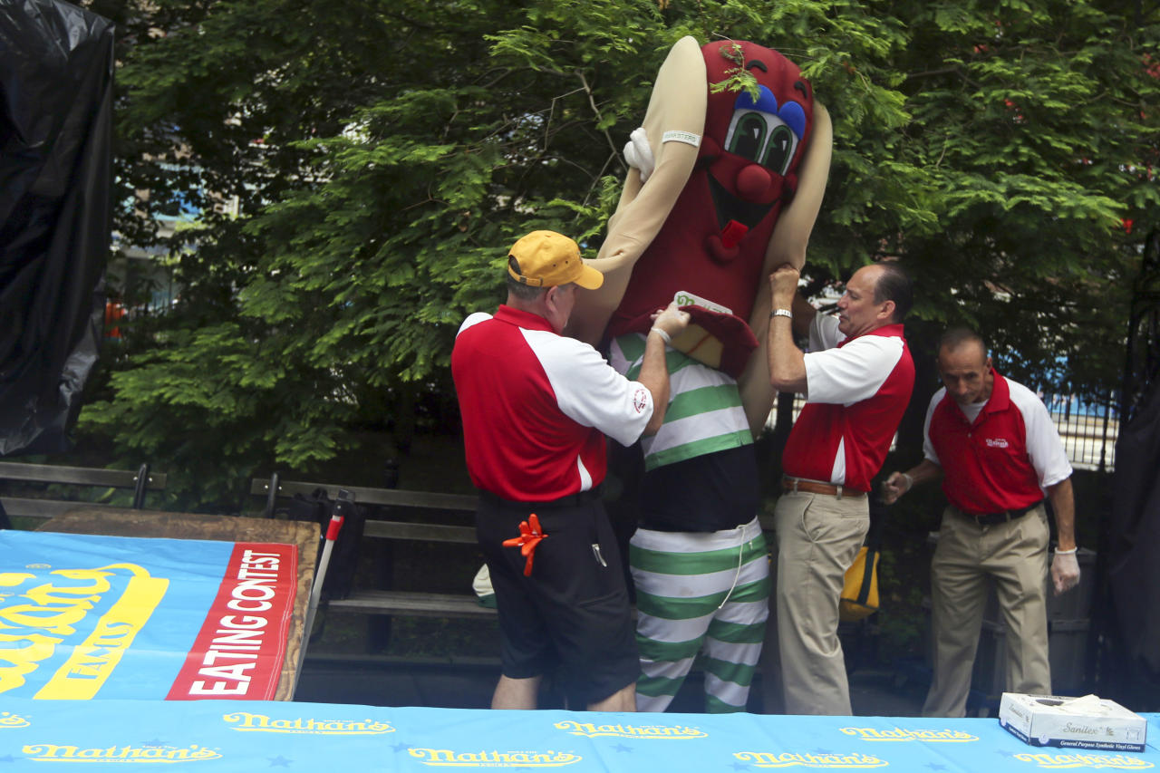 Nathan's employees help the mascot get into his costume before the official weigh-in for the Nathan's Fourth of July hot dog eating contest, Wednesday, July 3, 2013 at City Hall park in New York. (AP Photo/Mary Altaffer)