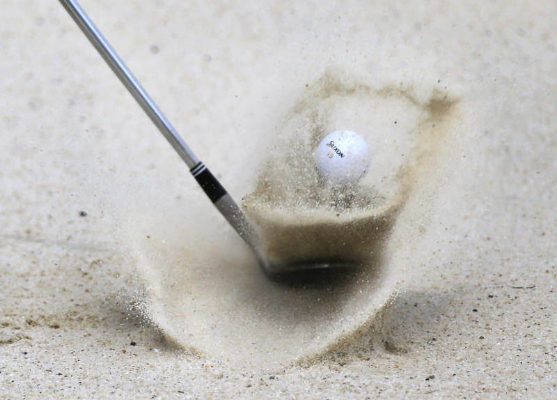 A club wielded by Vijay Singh, of Fiji, lifts a ball from a bunker on the eighth hole during a practice round for the PGA Championship golf tournament at Oak Hill Country Club, Wednesday, Aug. 7, 2013, in Pittsford, N.Y. (AP Photo/Julio Cortez)