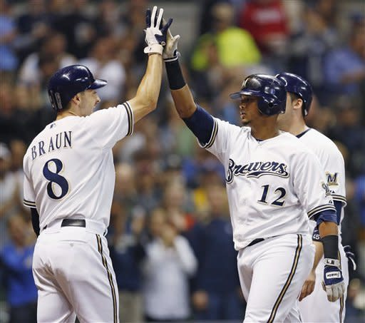 Milwaukee Brewers' Ryan Braun, left, gives a high-five to Martin Maldonado after Maldonado hit a grand slam off of San Diego Padres' Anthony Bass during the third inning of a baseball game Tuesday, Oct. 2, 2012, in Milwaukee. (AP Photo/Tom Lynn)