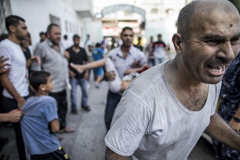 The father of a Palestinian girl screams as a relative carries her into the Kamal Adwan hospital in Beit Lahia, after she was injured by an Israeli strike on the northern Gaza Strip, on July 22, 2014