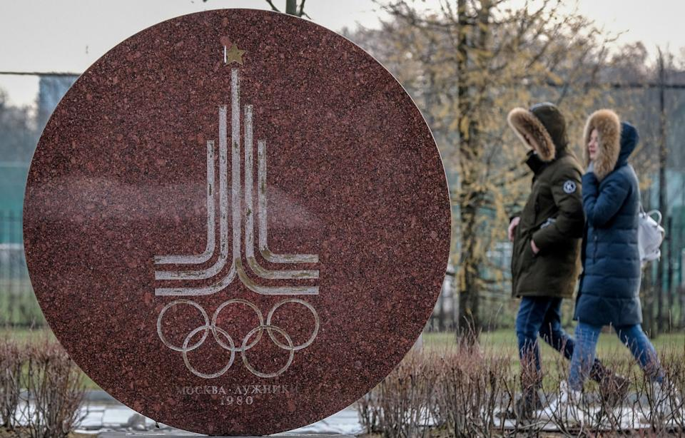 A couple walks behind a monument featuring the emblem of the 1980 Moscow Olympics near the Luzhniki stadium in Moscow on December 6, 2019. - The executive committee of the World Anti-Doping Agency will meet in Lausanne on December 9 to consider a recommendation for the ban, which would exclude Russians from major sports events including the 2020 Tokyo Olympics and 2022 Beijing Winter Olympics. A WADA review panel has accused Moscow of falsifying laboratory data handed over to investigators as part of a probe into the doping allegations that have plagued Russia for years. (Photo by Yuri KADOBNOV / AFP) (Photo by YURI KADOBNOV/AFP via Getty Images) (Photo: Getty Editorial)