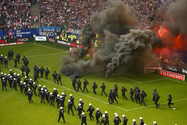 Soccer Football - Bundesliga - Hamburger SV v Borussia Moenchengladbach - Volksparkstadion, Hamburg, Germany - May 12, 2018 Hamburg fans let off flares and throw smoke bombs on to the pitch as riot police line up across the pitch REUTERS/Morris Mac Matzen DFL RULES TO LIMIT THE ONLINE USAGE DURING MATCH TIME TO 15 PICTURES PER GAME. IMAGE SEQUENCES TO SIMULATE VIDEO IS NOT ALLOWED AT ANY TIME. FOR FURTHER QUERIES PLEASE CONTACT DFL DIRECTLY AT + 49 69 650050 TPX IMAGES OF THE DAY