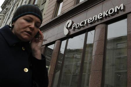 A woman passes by an office of Russian telecoms firm Rostelecom in Moscow