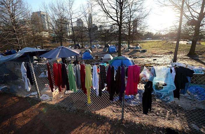 Personal items are hung on a fence at the tent encampment near Graham Street in Charlotte, NC on Friday, February 19, 2021. Residents of tent encampment are being required to vacate the area after health risks from rodent infestation was found in the area.